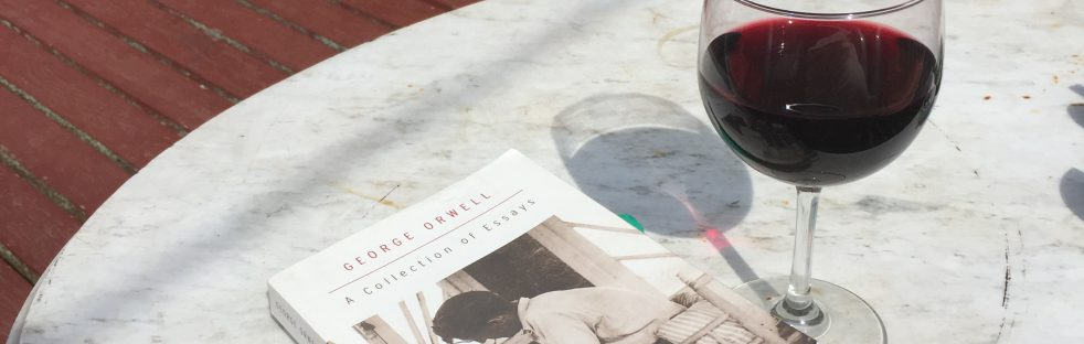 book and red wine on a marble table