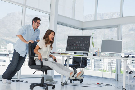 a laughing man pushes a laughing woman in a chair in an office